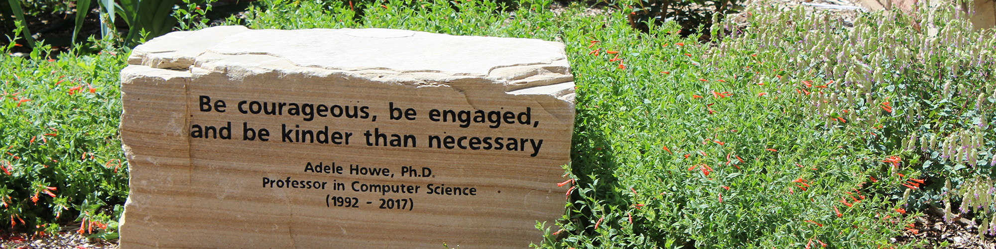 "A stone bench sits among green plants inscribed with the words ""Be courageous, be engaged, and be kinder than necessary"""