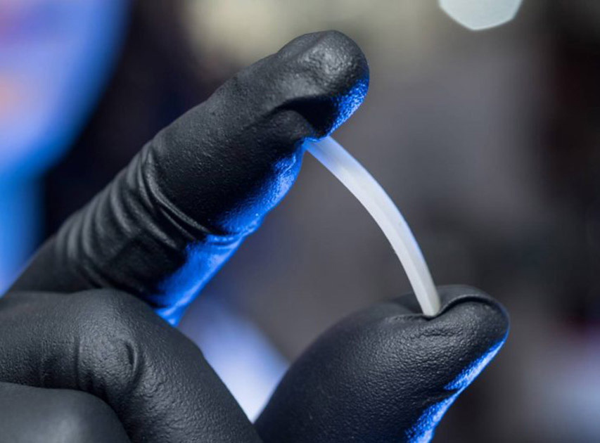 A researcher holds a small piece of polymer.